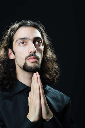 Young man praying in darkness photo