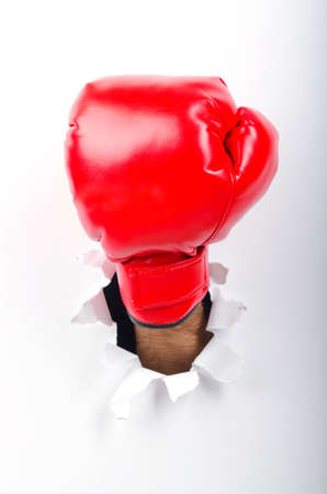 Hand in boxing glove through paper hole Stock Photo