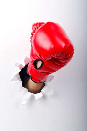 work glove: Hand in boxing glove through paper hole Stock Photo