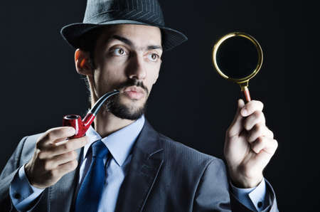 Detective with magnifying glass and pipe photo