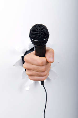 Hand holding microphone through hole in paper photo