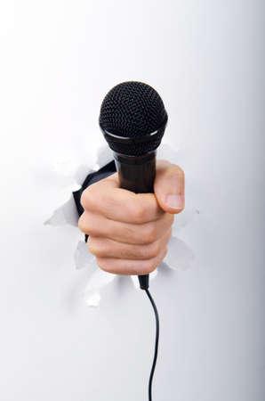 microfono antiguo: Mano que sostiene el micr�fono a trav�s del agujero en el papel