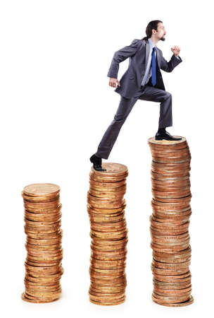 Businessman climbing gold coins stacks photo