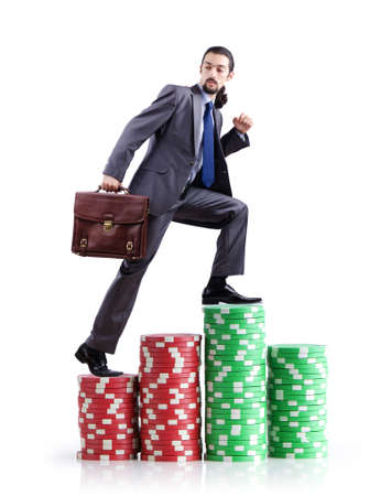 Stacks of casino chips and climbing businessman photo