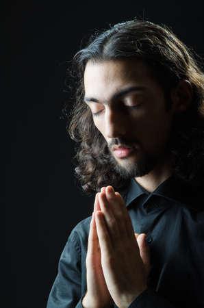 praise god: Young man praying in darkness