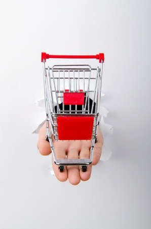 Shopping cart through hole in paper Stock Photo - 13224463