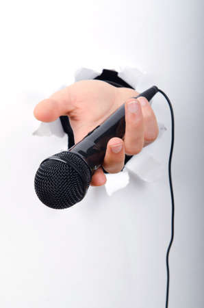 micro recording: Hand holding microphone through hole in paper