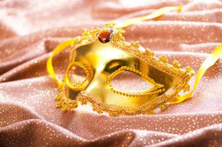 Golden mask on the satin background photo