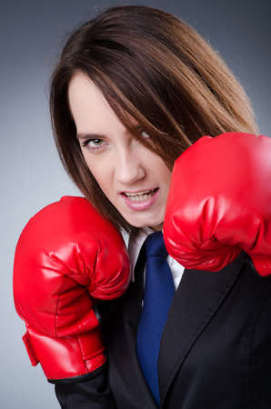 Young businesswoman in boxing concept photo