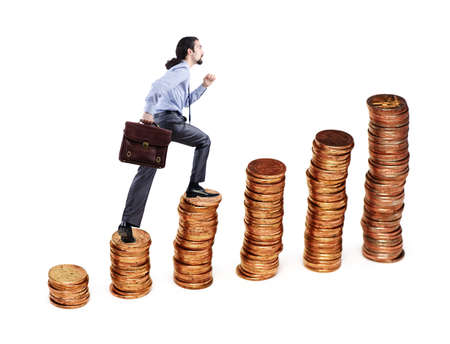 Businessman climbing gold coins stacks photo