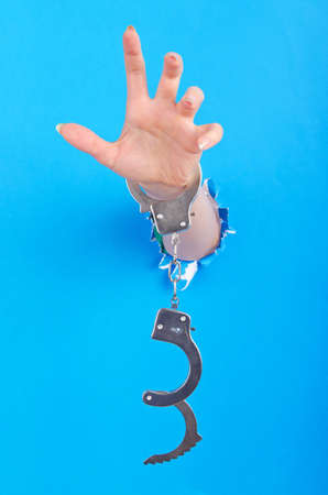 Hand with handcuffs out of paper photo