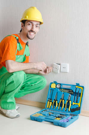 Electrician repairman working in the house photo
