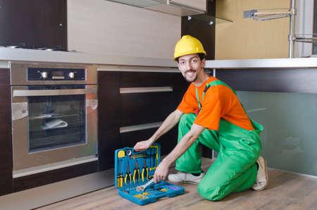 Repairman assembling the furniture at kitchen Stock Photo - 13888616
