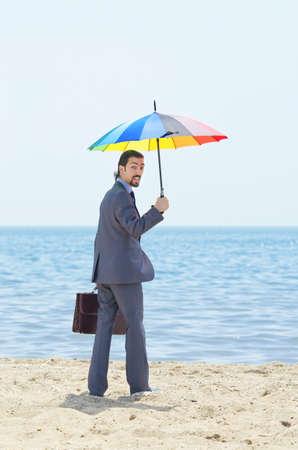 Man with umbrella on beach Stock Photo - 14385722