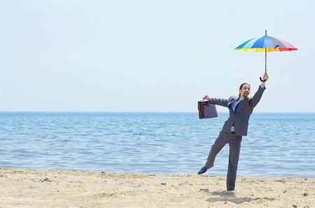 Man with umbrella on beach Stock Photo - 14385774