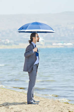 Man with umbrella on seaside beach Stock Photo - 14385757