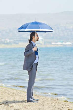Man with umbrella on seaside beach Stock Photo - 14385757