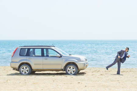 inconvenient: Man with car on seaside