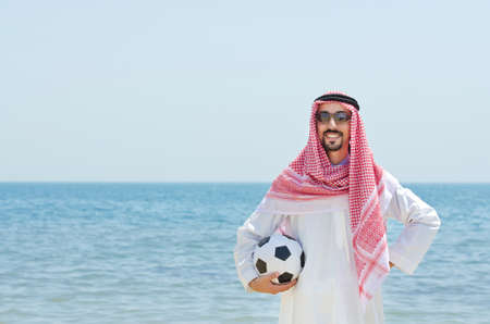 Arab with footbal at seaside photo