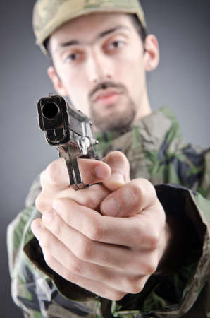 Soldier with gun in studio shooting photo