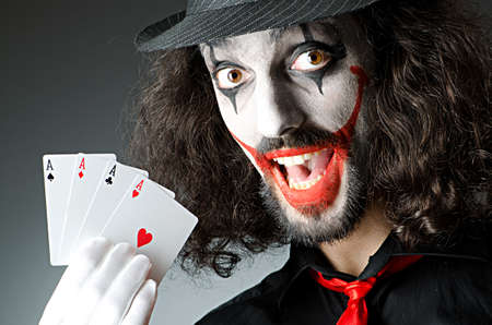 harlequin clown in disguise: Joker with cards in studio shoot