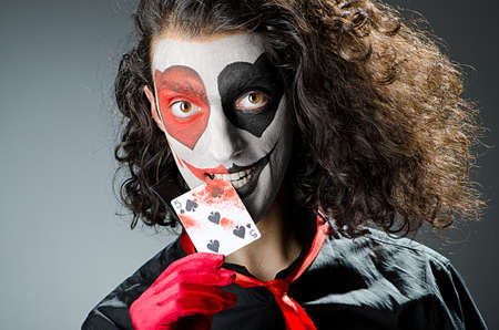 harlequin clown in disguise: Joker with face mask in studio