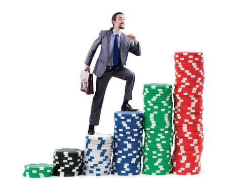 top: Businessman climbing stacks of casino chips Stock Photo