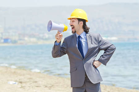 Man wearing helmet speaks with megaphone photo