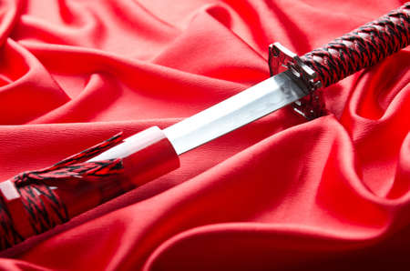 traditional weapon: Japanese sword takana on red satin background Stock Photo