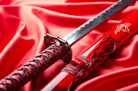 war decoration: Japanese sword takana on red satin background Stock Photo