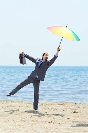 Man with umbrella on beach Stock Photo - 14385180