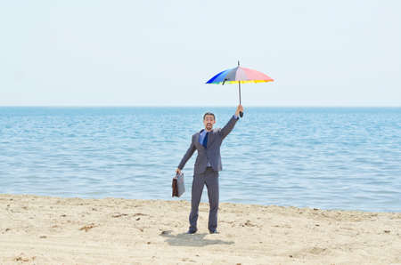 Man with umbrella on beach Stock Photo - 14385381