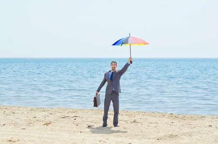 Man with umbrella on beach Stock Photo - 14385381