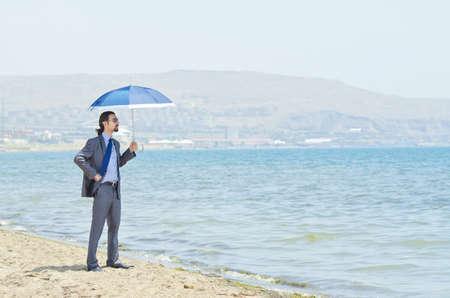 Man with umbrella on seaside beach Stock Photo - 14385307