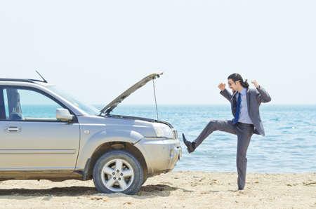broken car: Man with car on seaside