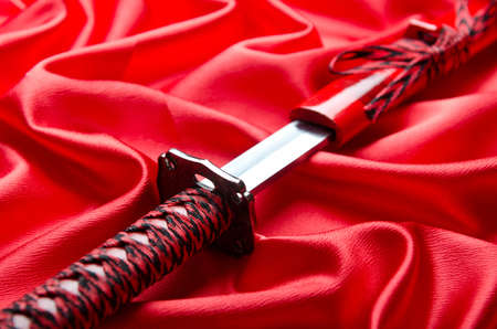 Japanese sword takana on red satin background photo