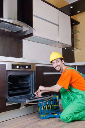Repairman assembling the furniture at kitchen photo