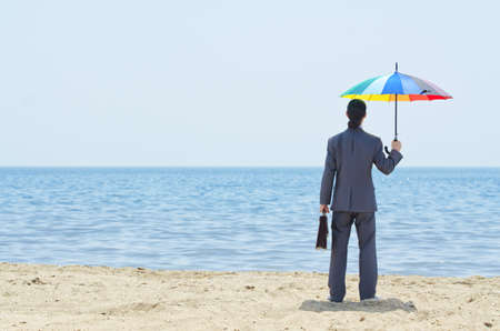 Man with umbrella on beach Stock Photo - 14425561