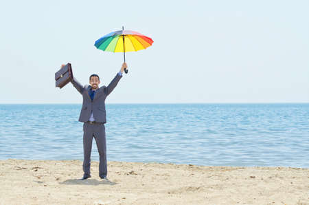 Man with umbrella on beach Stock Photo - 14703736