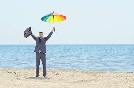 Man with umbrella on beach Stock Photo - 14703736