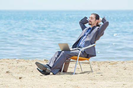 Businessman working on laptop on seaside photo