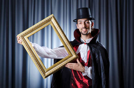 Magician with photoframe in studio photo