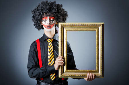 Clown with picture frames in studio