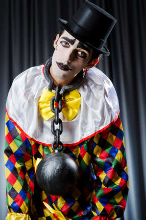 Clown with shackles in studio photo