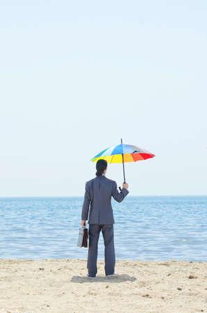 Man with umbrella on beach Stock Photo - 14725306