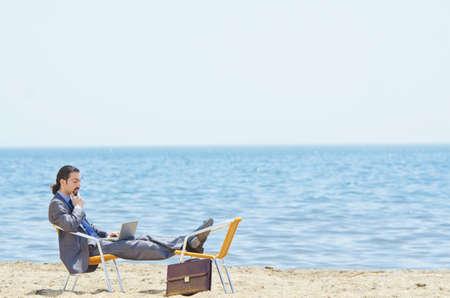 Businessman working on laptop on seaside photo