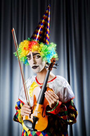 Clown playing on the violin photo