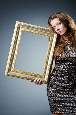 Young woman with picture frame on white photo