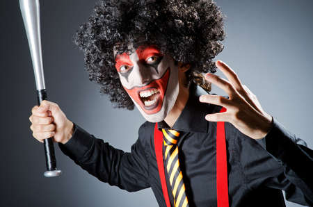 Funny clown with bat in studio photo