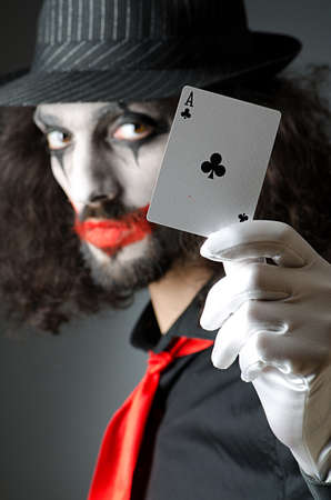 harlequin clown in disguise: Joker with cards in studio shoot
